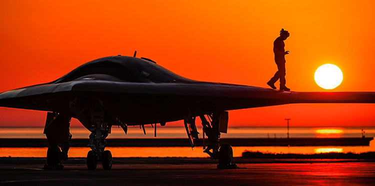 Someone walking over the wing of an X-47B autonomous drone at dusk